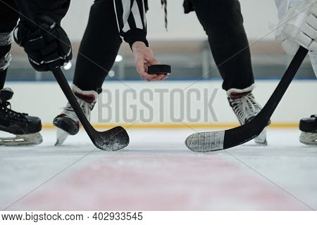 Hand of referee holding puck over ice rink with two players with sticks standing around and waiting for moment to shoot it