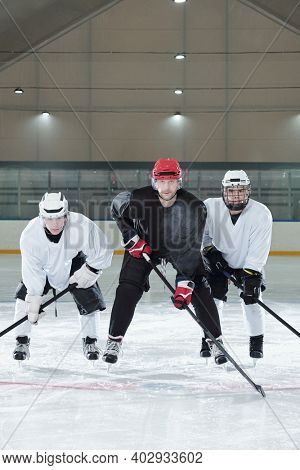 Three contemporary hockey players in sports uniform, gloves, skates and protective helmets bending forwards while training on ice rink before play