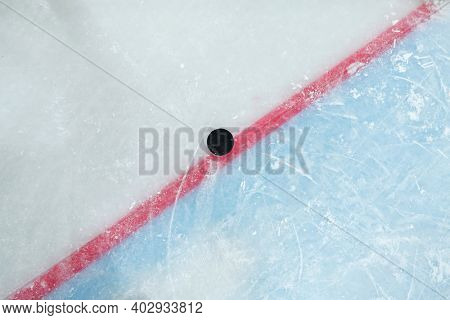 Puck lying on red line dividing play space and zone of net on ice rink for playing hockey that can be used as background