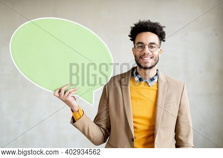 Cheerful mixed-race businessman looking at you with toothy smile while standing in front of camera and showing blank dusty green speech bubble