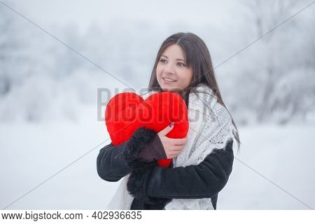 Beautiful girl with a red heart on the street in winter. Valentine's day February 14th. Woman outdoors against the backdrop of a magical winter landscape.