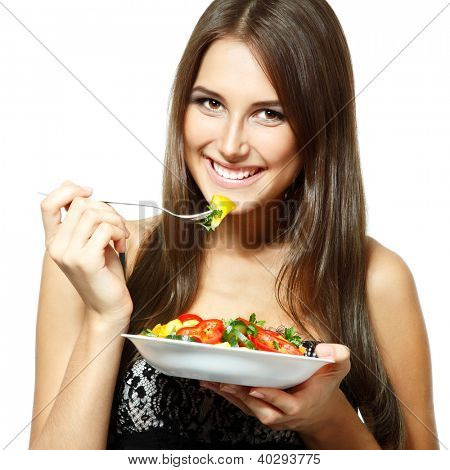Young funny woman eating salad over white background