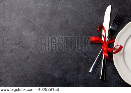 Valentines day background with empty plate and silverware. Top view flat lay with copy space