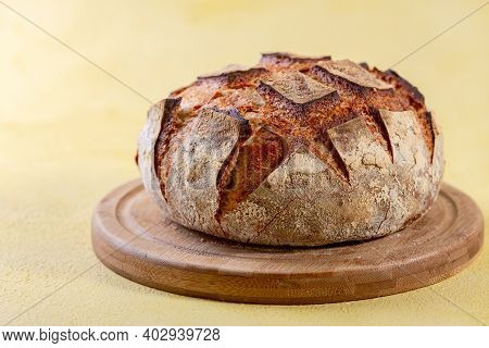 Artisanal Wheat Bread On Sourdough With The Addition Of Rye Flour On A Wooden Board. Concept Of Home