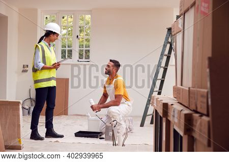 Female Surveyor With Digital Tablet Meeting With Decorator Working Inside Property