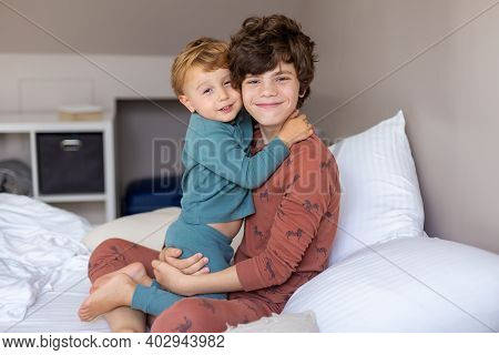 Brothers Sitting In A Bed In The Morning After Waking Up And Hugging. Tender Big Brother. Happy Fami