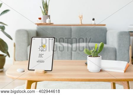 Digital tablet screen with a smart home controller on a wooden table
