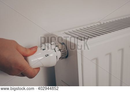 A Woman's Hand Turns The Battery Heating Knob. Heating In An Apartment, At Home. Heating Prices.