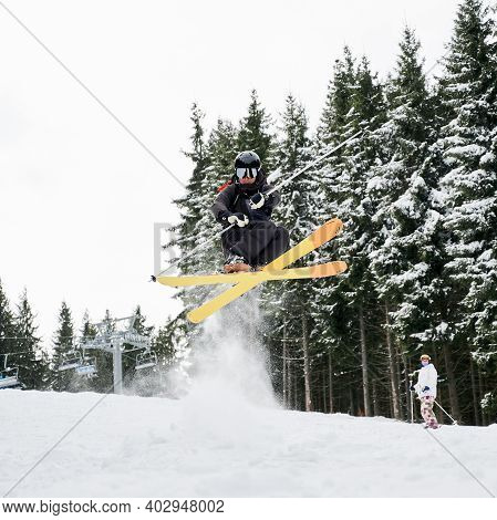 Male Skier In Ski Suit And Helmet Skiing On Fresh Powder Snow With Snowy Pine Trees On Background. M