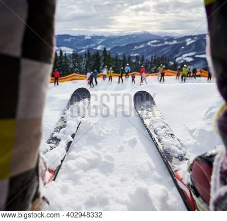 Close Up Of Man On Skis Standing On White Deep Snow At Ski Resort. Alpine Skis Attached To Ski Boots