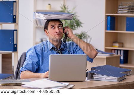 Young businessman employee unhappy with excessive work in the o