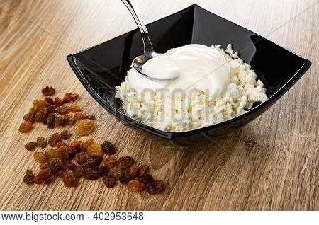 Scattered Raisin, Spoon In Black Glass Bowl With Defatted Grainy Cottage Cheese And Sour Cream On Br