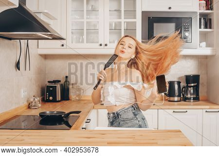 Woman Singing And Dancing In The Kitchen With A Smartphone, Music.a Girl In Headphones With A Phone