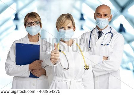 Shot Of Female And Male Doctors Standing Together On The Clinic's Foyer While Female Doctor Giving T