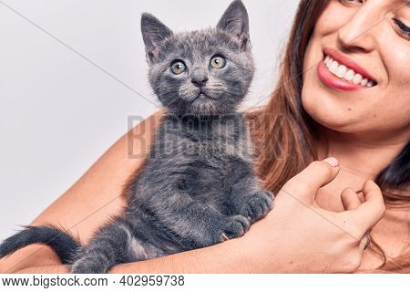 Young beautiful latin woman smilling happy. Standing with smile on face holding adorable cat over isolated white backgroun