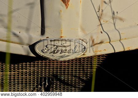 Regent, North Dakota, August 16, 2020: The Rusty Ford Tractor Hood Logo Is A Product Of The Ford Mot