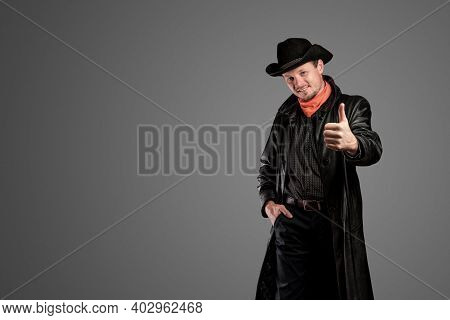 Cowboy In Leather Clothing Shows A Hand Gesture. Unshaven Smiling Man In A Hat And Cloak. Macho Guy