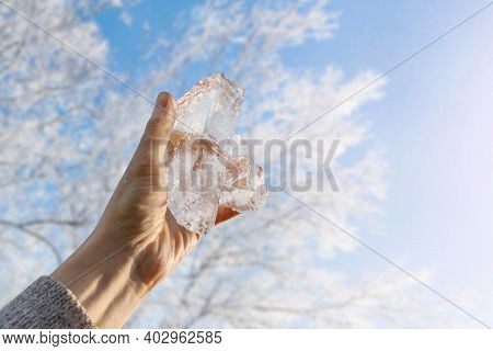 Piece Of Ice In The Hand Of A Man Against The Background Of Winter Trees And The Bright Sun. Cooling