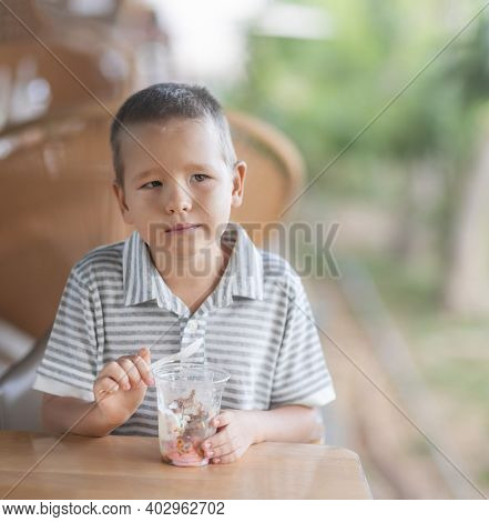 Cute boy eating ice-cream in outdoor cafe