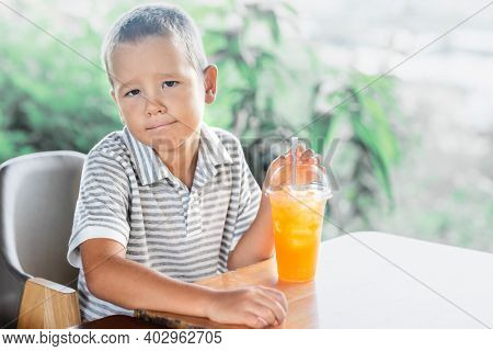 Cute boy drinking juice in outdoor cafe