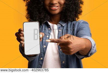 Black Woman Pointing At Smartphone With Empty Screen In Her Hand, Cropped. Unrecognizable African Am