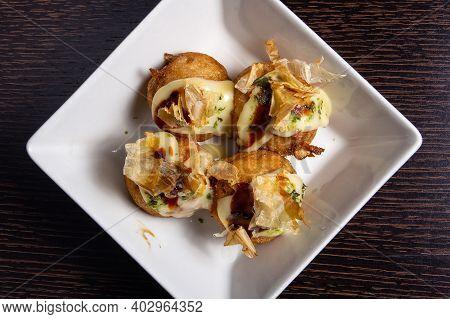 Chinese Dish Called Tako Yaki On A White Plate At Restaurant
