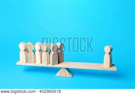 Human Figurine Has Equal Weight Against A Group Of People. Authoritative And Important. Highly Quali