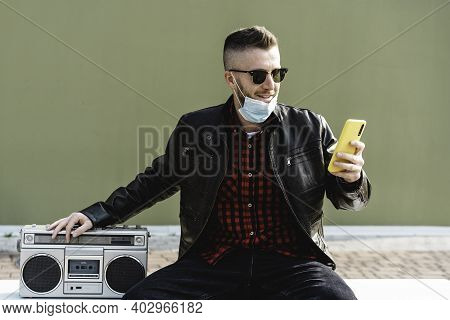 Man Video Calling Against Green Wall Background While Listening Music With A Retro Boombox - Cool Ma