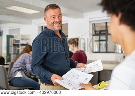 Happy mature professor giving corrected answer sheets to student in class. Rear view of black guy receiving exam test result in college classroom. Smiling proud teacher man returning test to students.