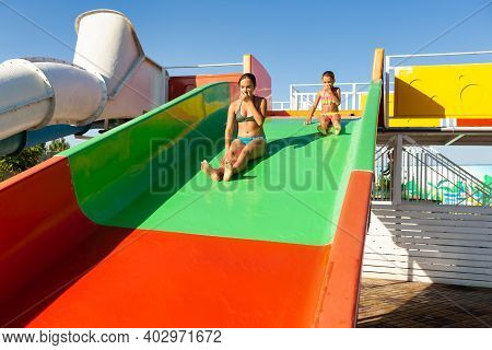 Two Lovely Cute Fun Sisters Descend From A Colorful Bright Slide Into A Pool With Clear Transparent