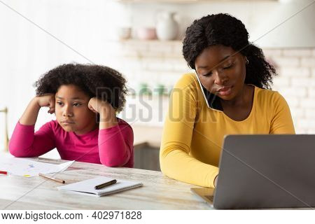 Lack Of Attention. Bored Little Black Girl Sitting Next To Her Busy Mom Working With Laptop And Cell