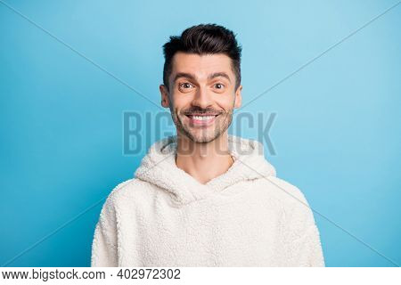 Photo Portrait Of Man In Woolen Hoodie With Stubble Smiling Isolated On Pastel Blue Colored Backgrou