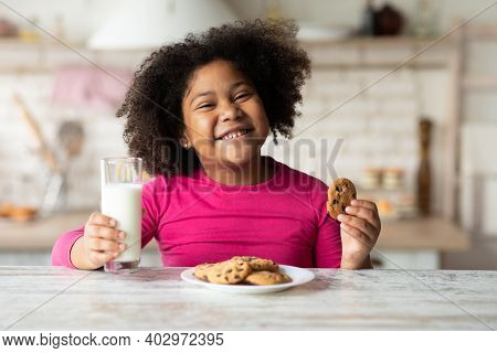 Portrait Of Cute African American Girl Enjoying Cookies And Milk In Kitchen, Pretty Black Child Eati