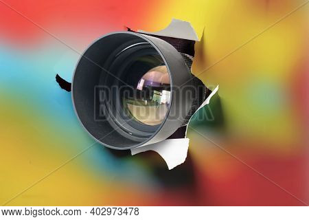 Concept Of Paparazzi Or Hidden Camera, Camera Lens Looks Out Through A Hole In Colorful Background
