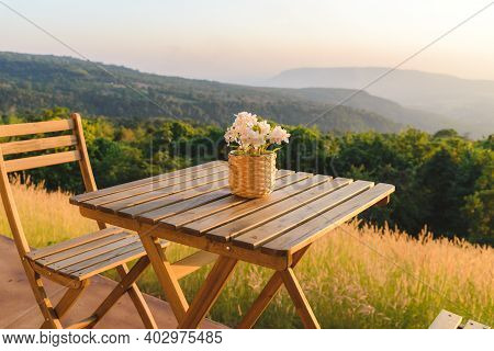 Flowerpot On Wooden Table And Chairs On Terrace. Beautiful Seating With Landscape Mountains View Whi