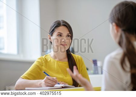 Attentively Listening Young Woman Psychologist Sitting At Table