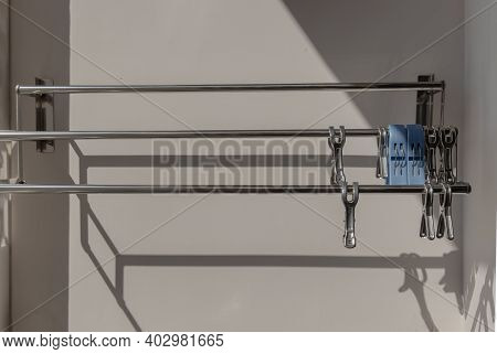 Empty Clothes Drying Rack And Stainless Steel Clothes Clips Hanging On The Wall In Outside Balcony O
