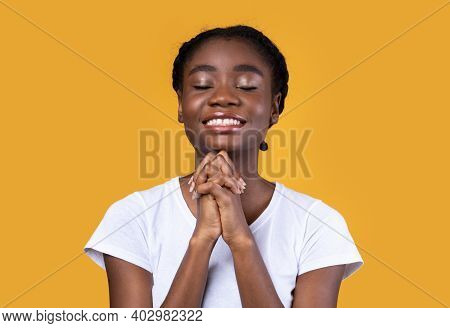 African American Woman Praying Holding Hands In Prayer Gesture Standing On Yellow Studio Background,