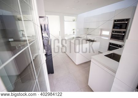 White Organised Kitchen With Modern Elements In An Apartment . High Quality Photo