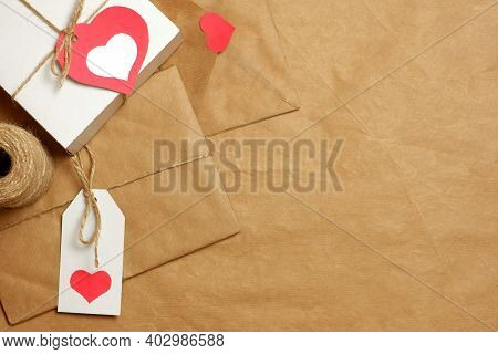 Gifts And Envelope Wrapped In Brown Craft Paper, Tied With Twine With Bows And Labels, Hearts And Co