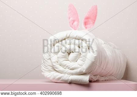 On The Table Lies A Folded Warm Duvet With Easter Bunny Ears. Blanket For The Bed. Copy Space.
