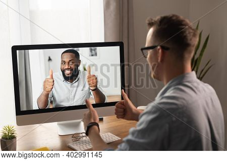Video Call, Video Meeting. A Young Man Is Discussing Some Business Tasks With A Young African Man Vi