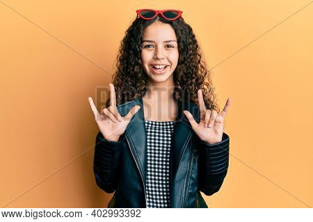 Teenager hispanic girl doing rock gesture smiling and laughing hard out loud because funny crazy joke.