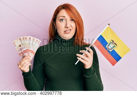 Beautiful redhead woman holding colombia flag and 10 colombian pesos banknotes clueless and confused expression. doubt concept.