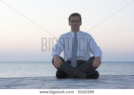 Businessman Meditating By The Sea