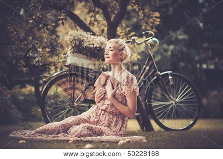 Dreaming blond retro woman with a book sitting on a meadow