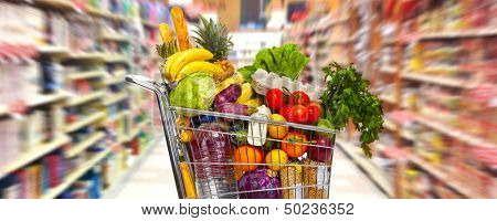 Full shopping grocery cart in supermarket.