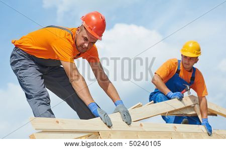 Two construction roofer carpenter worker installing wood board roof