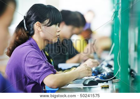 female chinese worker woman testing production at line conveyor in china factory manufacturing