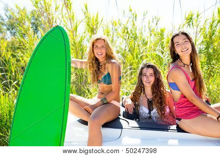 surfer beautiful girls group holding happy surfboards on convertible car